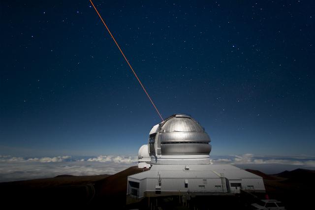Телескоп обсерватории Джемини на Гавайях направил лазерный луч в ночное небо, чтобы создать искусственную звезду, которую астрономы используют для калибровки изображения (фото Gemini Observatory/Association of Universities for Research in Astronomy).
