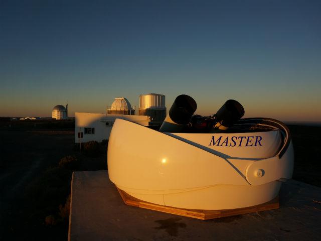 Российский телескоп-робот МАСТЕР-SAAO в ЮАР на фоне самого большого в Южном полушарии телескопа SALT с зеркалом диаметром 10,4 метра (левее вдали) (фото Евгений Горбовский/проект МАСТЕР).