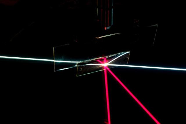 Прямоугольный образец, на который проецируются лучи разнх направлений. Белый луч проходит сквозь образец, как если бы он представлял собой прозрачное стекло. Падающий под другим углом красный луч отражается, как если бы образец был зеркалом (фото Weishun Xu, Yuhao Zhang).